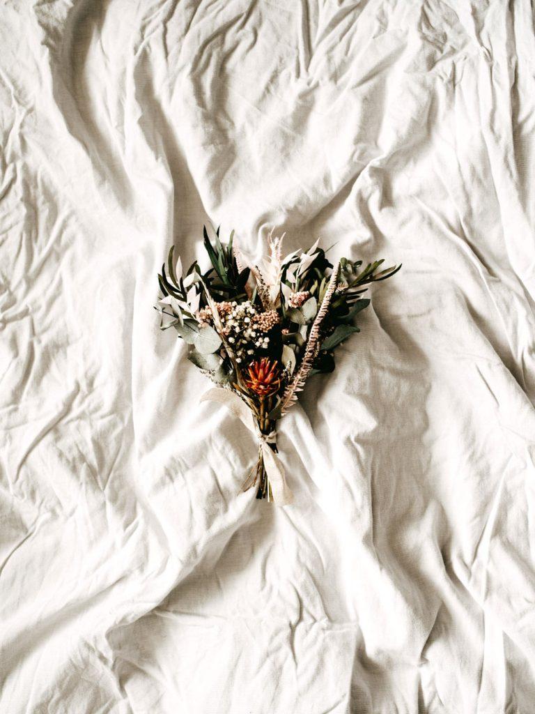 זר פרחים קטן על מצעים לבנים