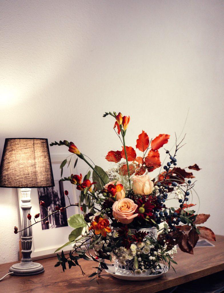 זר פרחים מונח על שולחן ומנורה