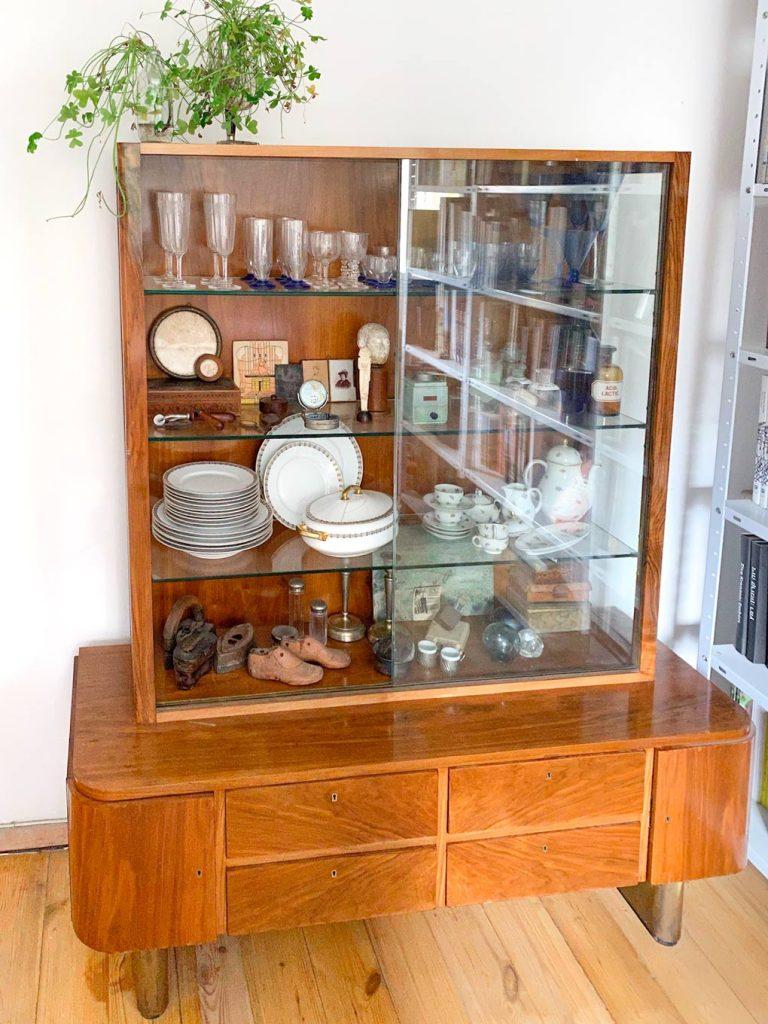 ויטרינת וינטאג׳ מעץ עם דלתות זכוכית והרבה פריטי וינטאג׳ בה