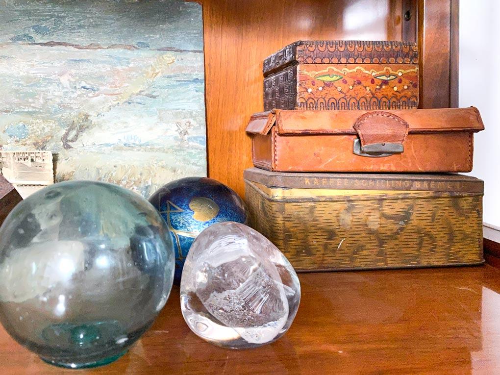 קופסאות וכדורי זכוכית בתוך ויטרינת וינטאג׳