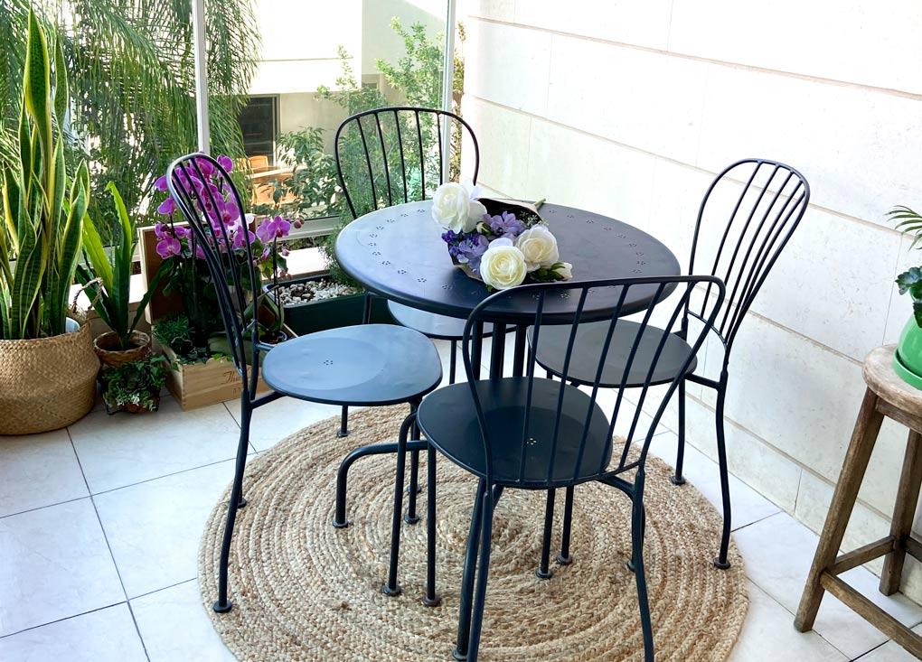 המרפסת לאחר השינוי, עם שולחן, כסאות, שטיח ועציצים