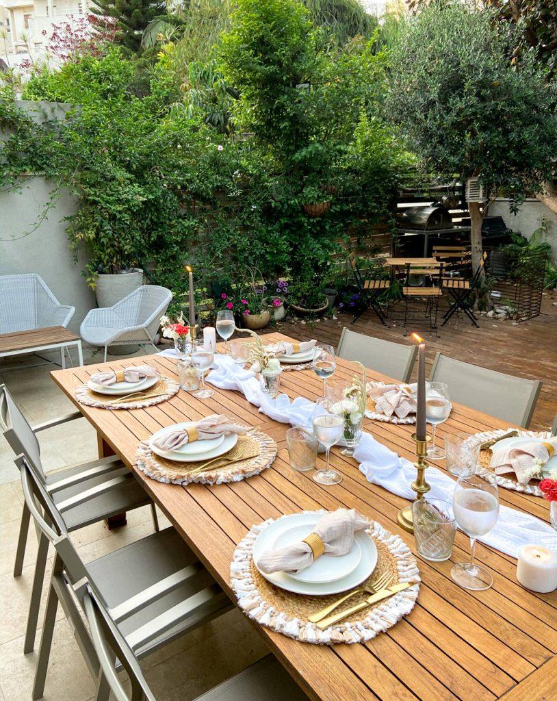 עריכת שולחן חג שבועות והגינה ברקע