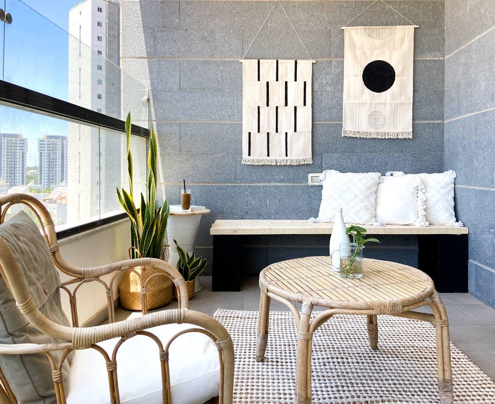 המרפסת החדשה, מבט לכיוון הקיר החדש: שולחן איקאה, כורסא, שטיח, ספסל ישיבה, כריות, שולחן צד ושטיחי קיר מצוירים diy