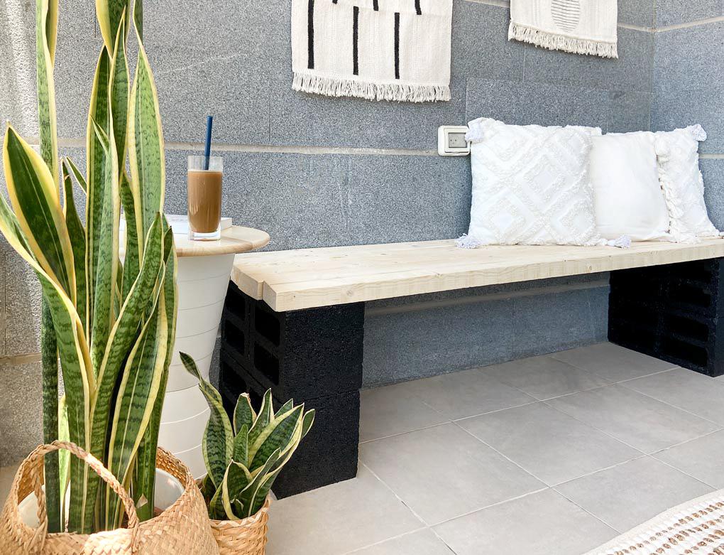 קלוז אפ על חלק מהספסל החדש, שולחן הקפה וצמחיה diy