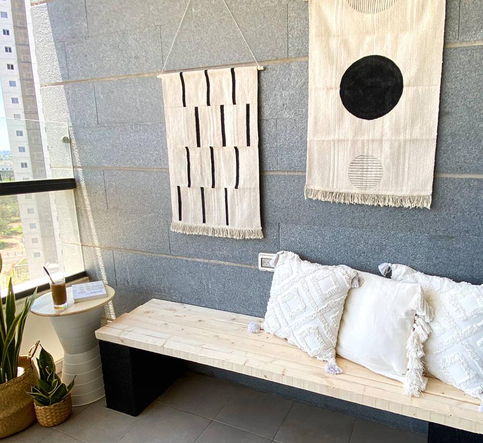 מבט לכיוון קיר המרפסת הכולל את שלושת פרויקטי ה־DIY: שולחן קפה, שטיחים צבועים וספסל ישיבה
